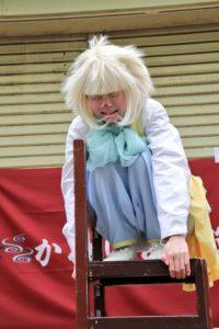 ピエロ(クラウン)のロイくんが椅子の上で泣きそうになっています。かめいど勝運大道芸2019で行われたアルジェントさーかすでのワンシーン